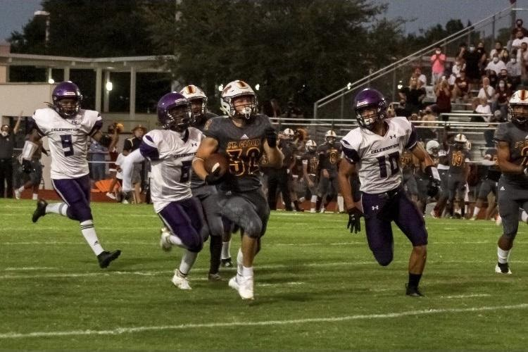 Rilling (32) sprints towards the end zone while dodging the members of the other team.