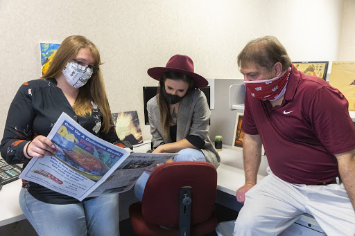 Kimberly Wethal (left) discusses a piece with her colleagues.