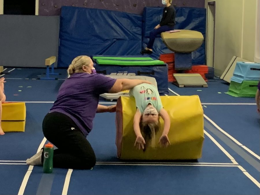 Instructor Shannon Suddeth helps a student learn a skill during a gymnastics class.