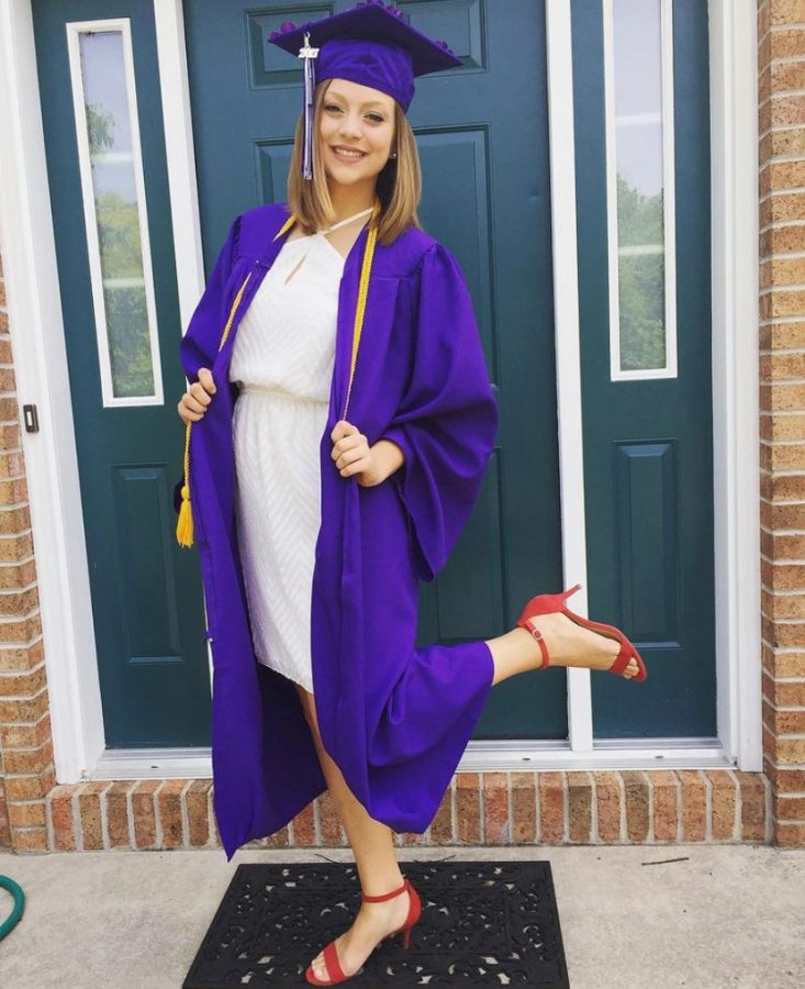 High+school+senior%2C+Madelyn+Falk%2C+poes+in+her+graduation+cap+and+gown+in+2017.+