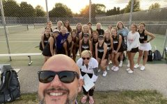 Model takes a photo with the Girls Tennis team.